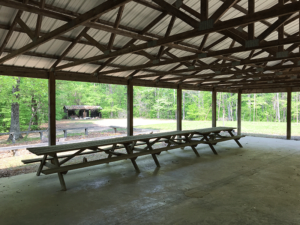 Three picnic tables lined end-to-end, along the west side of the shelter interior.