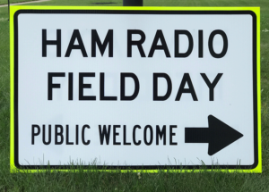 "A 2 foot high by 3 foot wide highway-styled sign, with black letters on a white background, edged in fluorescent yellow and a black border. The sign reads, ""HAM RADIO FIELD DAY, PUBLIC WELCOME""."