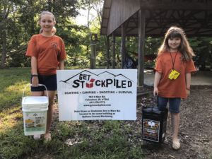 "Two young girls in matching orange Camp Moneto t-shirts, standing on either side of the white ""Get Stockpiled"" sign in front of the shelter. Each girl is holding a bucket of freeze-dried food."