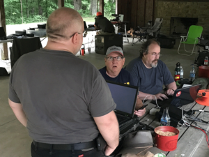 Photo taken inside the shelter. Operators are gathered around their equipment, having a discussion. Another operator is in the background with his back to the camera, operating an additional station.